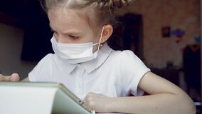 Caucasian preteen girl with medical mask on her face concentrated on her task with tablet. Concept of distance learning