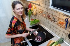 Caucasian pretty girl with a smile does the cooking in the kitch Royalty Free Stock Photo