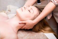 Caucasian pretty woman having massage in spa salon. Blonde women having facial massage in spa salon. close-up stock photo