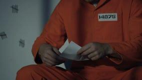 Caucasian prisoner reading letter from beloved, male criminal missing family stock video footage