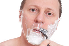 Caucasian with razor and shaving foam in his face Royalty Free Stock Photography
