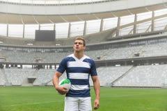 Caucasian rugbyspelareanseende med rugbybollen i stadion royaltyfri bild