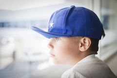 Caucasian sad boy in cap looks out the window. The boy is waiting near the window. Caucasian sad boy in cap looks out the window. The boy is waiting near the Royalty Free Stock Photo
