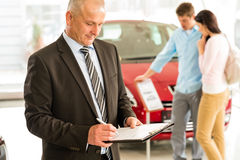 Caucasian salesman in car showroom Stock Image