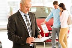 Caucasian salesman in car showroom. Portrait of Caucasian salesman in car showroom stock image