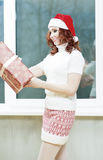 Caucasian Santa Girl Holding Christmas Box Gift. Portrait of Hap Royalty Free Stock Photo