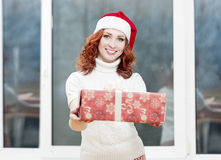 Caucasian Santa Girl Holding Christmas Box Gift. Portrait of Hap Stock Photos