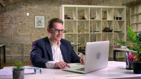 Caucasian satisfeito em sua mesa de trabalho usando o portátil ao sentar-se com tijolo verde atrás filme