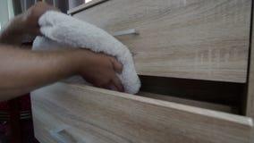 Caucasian satta fullständigt vikta handdukar för man händer efter tvätteri in i byrå Begrepp för hushållsysslor och arbetsuppgift lager videofilmer