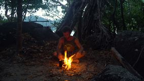 Caucasian Savage Man Burning Little Campfire in the Tropical Forest at Twilight to Boil Kettle with Rice for Dinner. 4k UHD stock footage