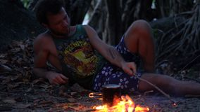 Caucasian Savage Man Burning Little Campfire in the Tropical Forest at Twilight to Boil Kettle with Rice for Dinner. 4k UHD stock video footage