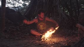 Caucasian Savage Man Burning Little Campfire in the Tropical Forest at Twilight to Boil Kettle with Rice for Dinner. Ritual Shamanism Dancing Around the Fire stock footage