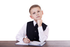 Caucasian school boy at his desk on white background with copy s Stock Photography