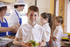 Caucasian schoolboy holds plate of food in school cafeteria Stock Photo