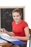 Caucasian schoolgirl by desk studying math exam. University or college female student sitting by the desk at math class. Blackboard with advanced mathematical Royalty Free Stock Image