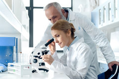 Caucasian scientists in white uniform working with microscope and reagents in chemical laboratory. Focused caucasian scientists in white uniform working with royalty free stock images