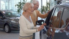 Senior couple looks inside the car at the dealership. Caucasian senior couple looking inside the car at the dealership. Aged blond women leaning her hands on the Stock Photos