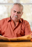 Caucasian senior man reading the daily newspaper Royalty Free Stock Images