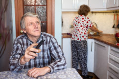 Caucasian senior man switches channels with TV remote control while sits at the table in kitchen, wife washing utensil Stock Photos
