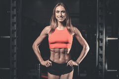 Caucasian fitness female model in gym close up abs stock photography