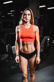 Caucasian fitness female model in gym close up abs stock image