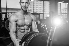 Caucasian fitness male model execute exercise with barbell. Brutal bodybuilder on diet resting and working out in the gym. Caucasian fitness male model execute stock photography