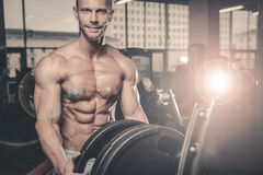 Caucasian fitness male model execute exercise with barbell. Brutal bodybuilder on diet resting and working out in the gym. Caucasian fitness male model execute stock images