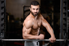 Caucasian fitness male model execute exercise with barbell. Brutal bodybuilder on diet resting and working out in the gym. Caucasian fitness male model execute royalty free stock images