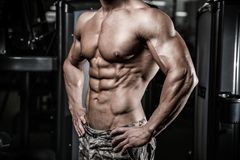 Caucasian fitness model in gym close up abs. Handsome caucasian fitness model in gym close up abs concept man on diet shirtless training six pack healthcare royalty free stock images