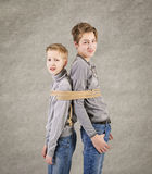 Caucasian siblings boys tying with rope. Isolated on gray background. Concept of emotions Royalty Free Stock Images