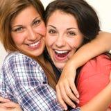 Caucasian sisters embracing, laughing at camera stock images
