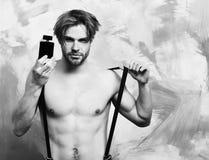 Caucasian skäggig macho man i flåsanden med hängslen som rymmer doft Arkivbilder