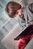 Caucasian skolpojke som bär elegant kläder genom att använda en digital minnestavla, medan sitta på en soffa hemma arkivbilder