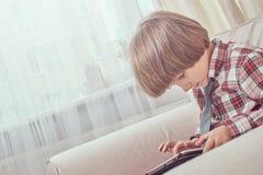 Caucasian skolpojke som bär en rutig skjorta med bandet genom att använda en digital minnestavla som hemma sitter på en soffa royaltyfri fotografi