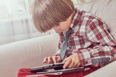 Caucasian skolpojke som bär en rutig skjorta med bandet genom att använda en digital minnestavla som hemma sitter på en soffa royaltyfri bild