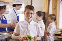 Caucasian skolpojkehållplatta av mat i skolakafeteria arkivfoto