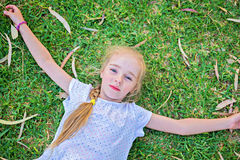 Caucasian small girl lay on grass Royalty Free Stock Photos