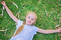 Caucasian small girl lay on grass Royalty Free Stock Photos