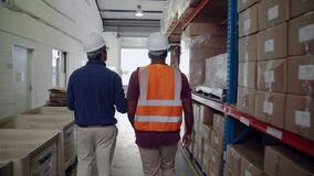 Manager and worker walking through isle double checking order of packaged parcels in factory warehouse