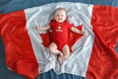 Caucasian smiling baby boy girl with blue eyes lying on large Canadian flag with red maple leaf