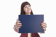 Caucasian Smiling Female Brunette Holding Blank Blue Plate for Text in Front. Focus on Board.Isolated Against White Stock Images