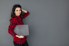 Caucasian smiling student girl holding laptop over gray background Royalty Free Stock Photo