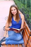Caucasian smiling student reading book Stock Photography
