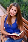 Caucasian smiling student reading book Royalty Free Stock Photos