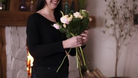 Caucasian, smiling woman - professional florist holding a half made bouquet and adding flowers and plants to composition. Designing, floral workshop, leisure stock footage