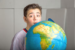 Caucasian smooth-skinned boy hidden behind globe on industrial b Stock Photos