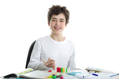 Caucasian smooth-skinned boy playing with dominoes on homework. Smiling Caucasian smooth-skinned boy wearing a white long sleeve t-shirt is playing with dominoes Stock Image