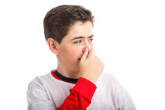 Caucasian smooth-skinned boy plugging his nose. A cute Caucasian smooth-skinned boy is plugging his nose because of bad smell Royalty Free Stock Photo