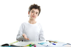 Caucasian smooth-skinned boy pointing homework with upwards palm. Calm Caucasian smooth-skinned boy wearing a white long sleeve t-shirt is pointing homework with Royalty Free Stock Image
