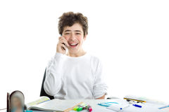 Caucasian smooth-skinned boy talking on cell phone on homeworks. Smiling handsome Caucasian smooth-skinned boy is talking on cell phone while doing homework and Royalty Free Stock Photography